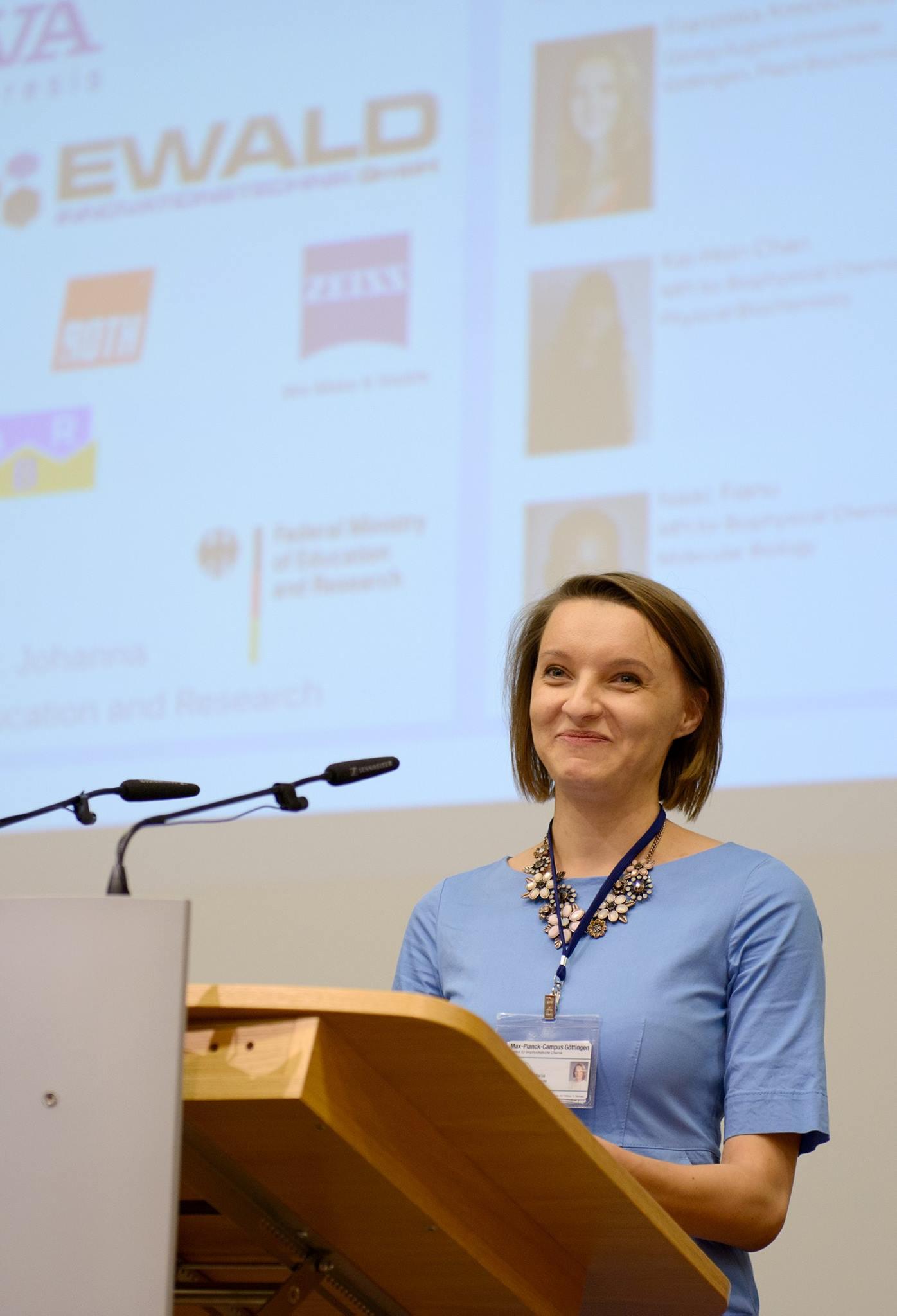 Vokietijos Biofizikinės chemijos Makso Planko institute biofizikos srityje daktaro laipsnį įgijusi kraštietė Marija Liutkutė ne tik dalyvauja mokslinėse konferencijose, bet ir pati jas organizuoja. Nuotraukoje – jaunoji mokslininkė sveikina 2017 metais savo surengtos studentų molekulinės biologijos konferencijos dalyvius. © Böttcher-Gajewski / Max-Planck-Institut für biophysikalische Chemie nuotr.